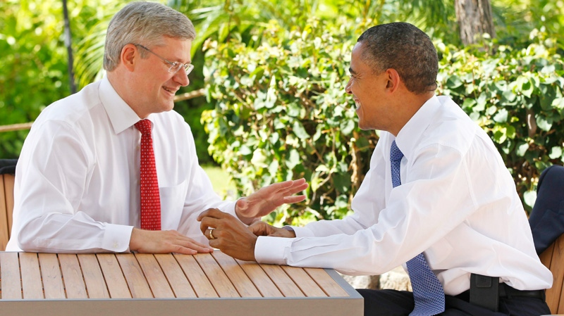 Prime Minister Stephen Harper, left, talks with U.S. President Barack Obama following the first plenary session of the Asia-Pacific Economic Cooperation summit in Kapolei, Hawaii, Sunday, Nov. 13, 2011. (AP / Charles Dharapak)