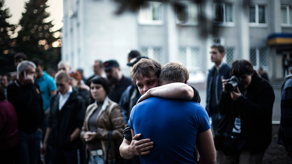 Two men react after Ukrainian national guardsmen opened fire on a crowd outside a town hall in Krasnoarmeisk, about 30 kilometers (20 miles) from the regional capital, Donetsk, Ukraine, Sunday, May 11, 2014. (AP / Manu Brabo)