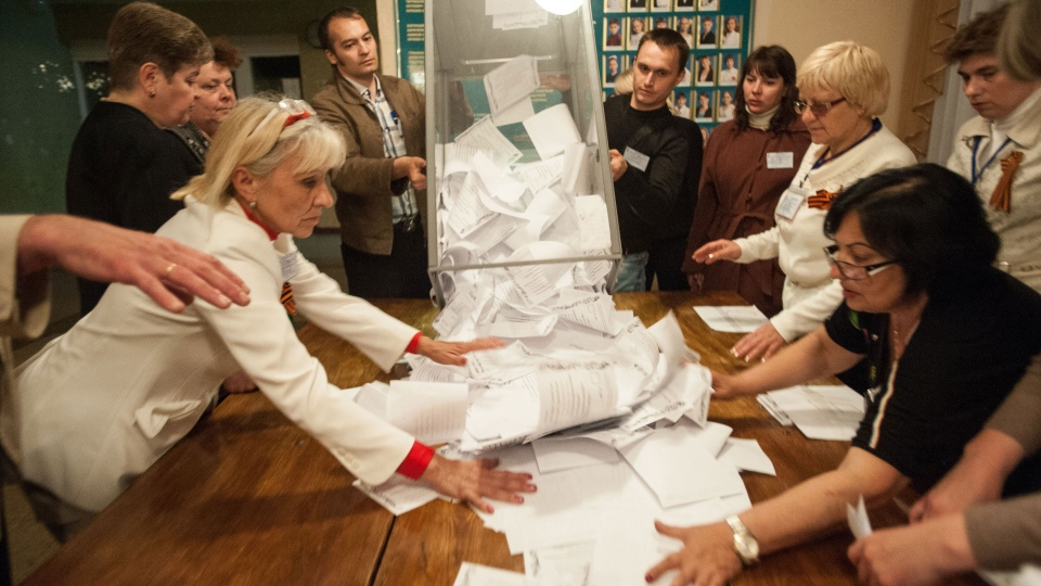 Members of election committee empty a ballot box after voting closed at a polling station in Donetsk, Ukraine, Sunday, May 11, 2014. (AP/ Evgeniy Maloletka)