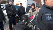 A protester from the Occupy Nova Scotia movement pushes a shopping cart loaded with personal effects through a row of police officers at the Grand Parade outside city hall in Halifax on Saturday, Nov. 12, 2011. (Andrew Vaughan / THE CANADIAN PRESS)