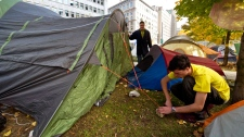 Mathieu Martin, right, relocates his tent with the help of Leonid Gorbov at the Occupy Montreal protest in Montreal's financial district Wednesday, Nov. 9, 2011. (Paul Chiasson / THE CANADIAN PRESS)