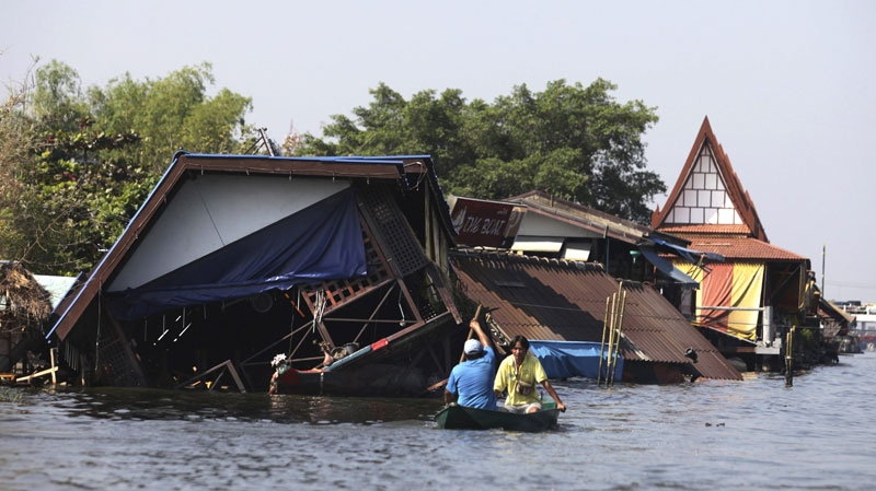 Thai men ride a boat next to a house damaged by flooding in Bangkok