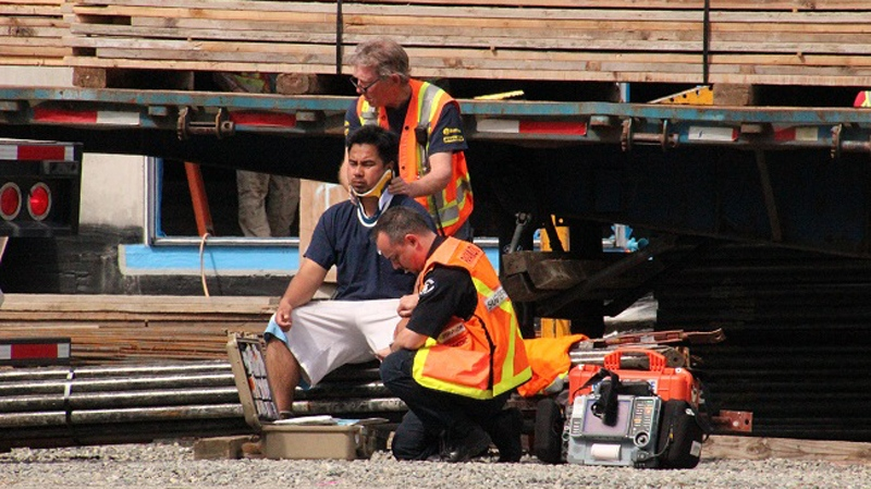 A construction worker is treated by first responders after an accident in Surrey on May 12, 2014. (CTV)