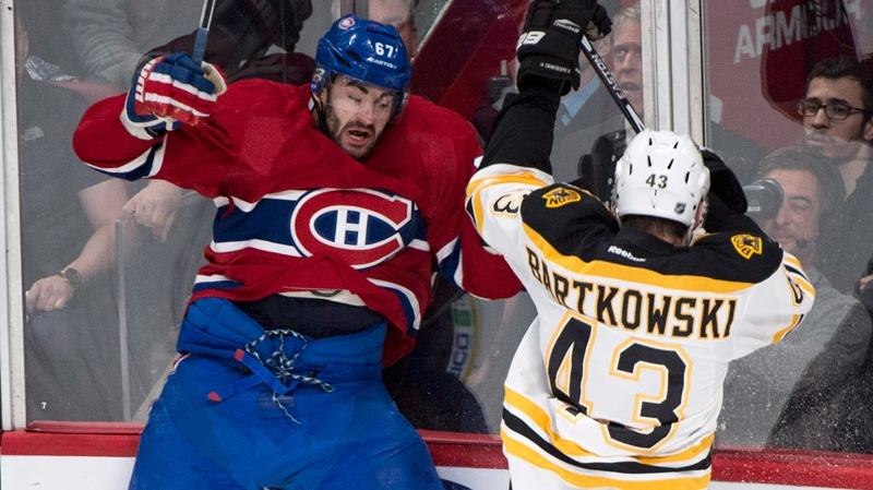 Montreal Canadiens' Max Pacioretty, left, is checked into the boards by Boston Bruins' Matt Bartkowski during first period NHL playoff hockey action on Monday, May 12, 2014 in Montreal. THE CANADIAN PRESS/Paul Chiasson
