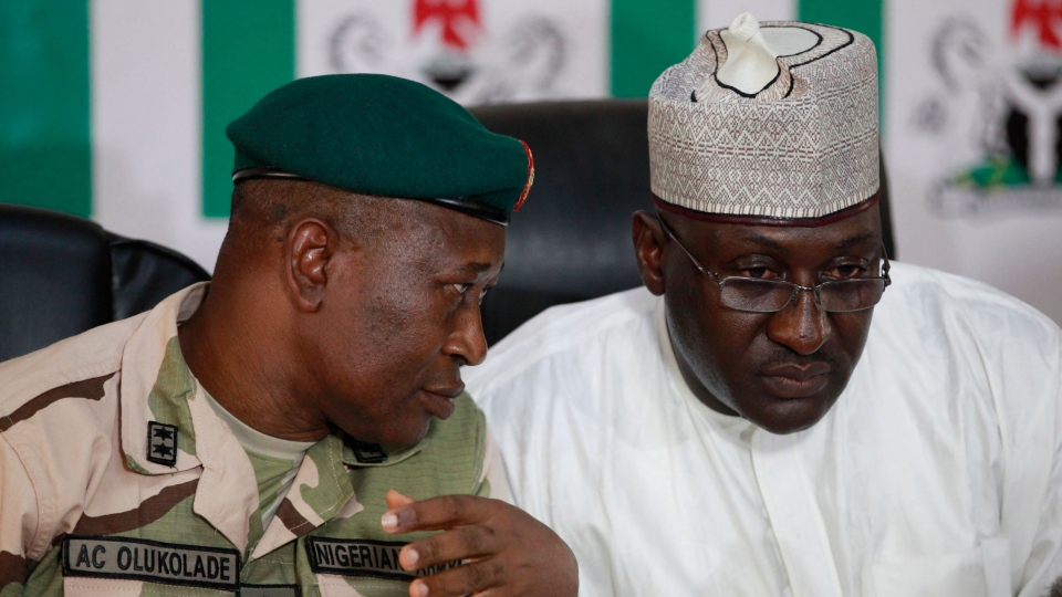 Brig. Gen. Chris Olukolade, Nigeria's top military spokesman, left, talks with Director General, National Orientation Agency, Mike Omeri, during a press conference on the abducted school girls in Abuja, Nigeria, Monday, May 12, 2014. (AP / Sunday Alamba)