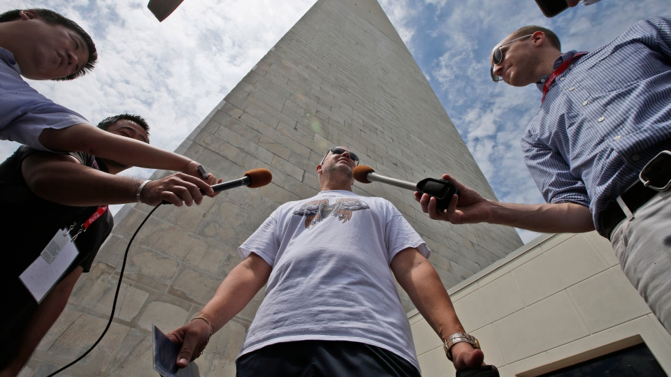 Marc Tanner, from Boca Raton, Fla., who was in the first group of tourists to visit the newly reopened Washington Monument, is interviewed by reporters after emerging from the monument in Washington on Monday, May 12, 2014. (AP)