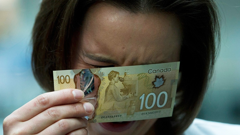 Martine Warren, a scientific advisor for the Bank of Canada has a close look at the bank's new circulating $100 bill, Canada's first polymer bank note, in Toronto on Monday Nov. 14, 2011. (Nathan Denette / THE CANADIAN PRESS)