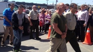 Tom Harding, Jean Demaitre and Richard Labrie are escorted by police from a van into the temporary courthouse in Lac-Megantic on May 13, 2014 (Maya Johnson/CTV Montreal)