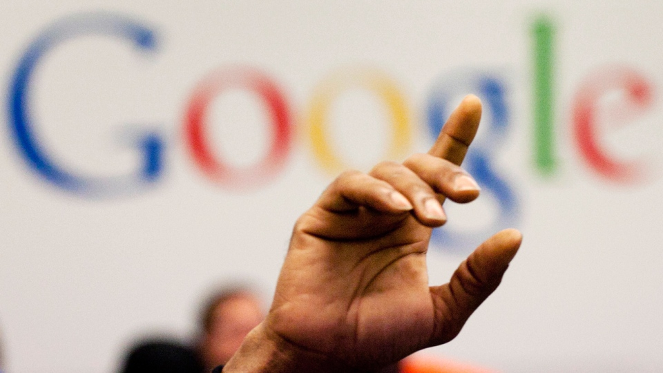 A man raises his hand during at Google offices in New York, Oct. 17, 2012. (AP / Mark Lennihan)