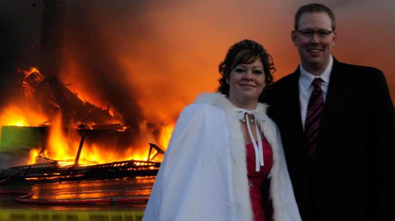 Mike and Nancy Rogers pose for wedding photographer Nicholas Augustus as White Point Beach Resort's main lodge burns in the background on Saturday, Nov. 12, 2011. (Nicholas Augustus / THE CANADIAN PRESS)