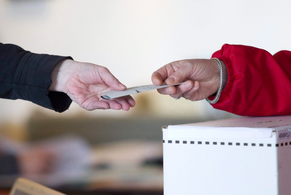 An election official hands back to a voter her marked ballot on May 2, 2011. (Chris Young / THE CANADIAN PRESS)