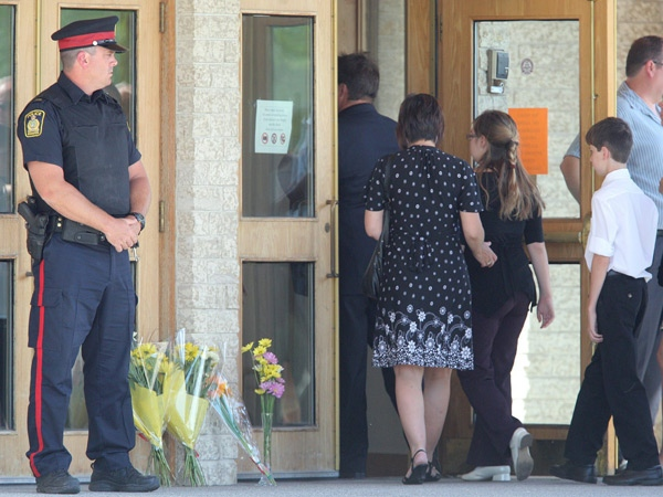 A Winnipeg Police Service officer watches the door at the funeral for Tim McLean at Westwood Community Church in Winnipeg on Saturday Aug. 9, 2008. Family and friends gathered Saturday to say goodbye to a young man who was stabbed and beheaded in a seemingly random attack aboard a Greyhound bus over a week ago. THE CANADIAN PRESS/Jason Halstead