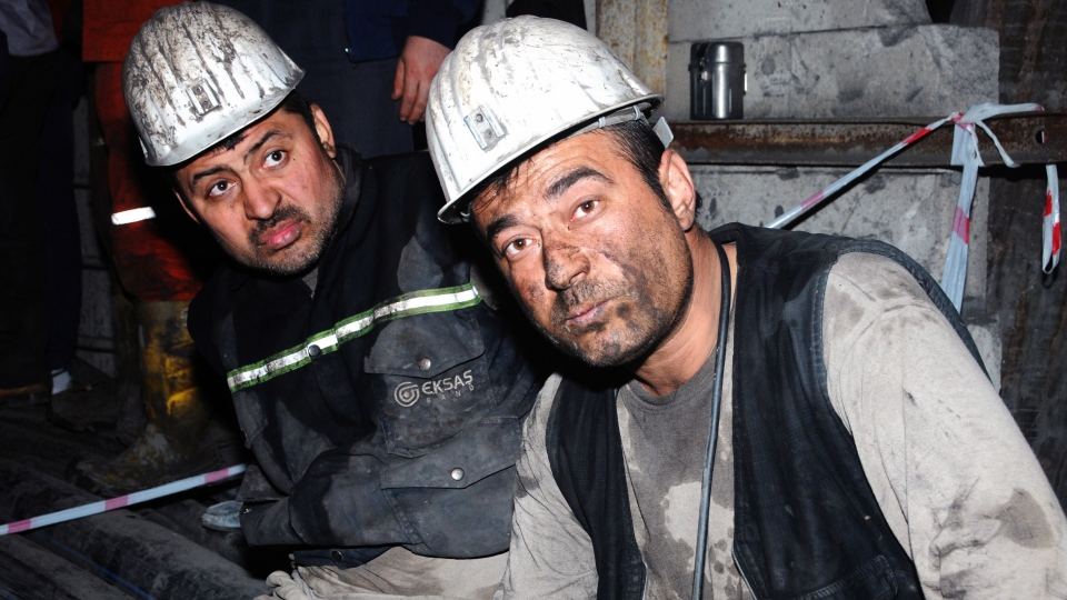 Two miners look around after being rescued hours after an explosion and fire at a coal mine killed at least 17 miners and left up to 300 workers trapped underground, in Soma, in western Turkey, late Tuesday, May 13, 2014. (AP)