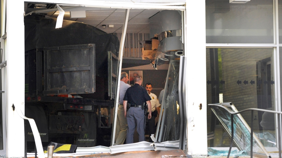 Police and WMAR-TV officials inspect damage caused by a vehicle that crashed into the television station's building Tuesday, May 13, 2014, in Towson, Md. (AP / Steve Ruark)