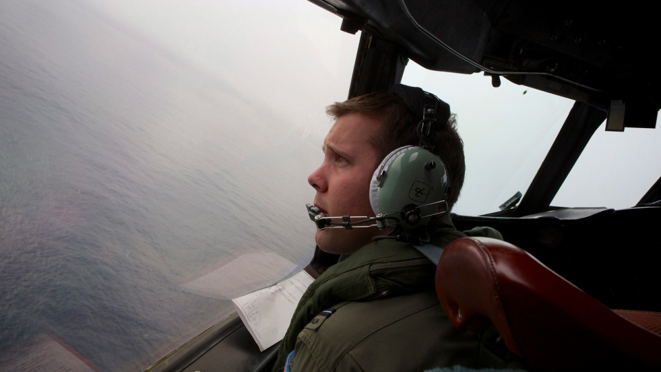 In this file photo, co-pilot, flying officer Marc Smith turns his Royal Australian Air Force AP-3C Orion aircraft at low level in bad weather whilst searching for missing Malaysia Airlines Flight 370 over the Indian Ocean, March 24, 2014. (AP / Richard Wainwright, Pool, File)