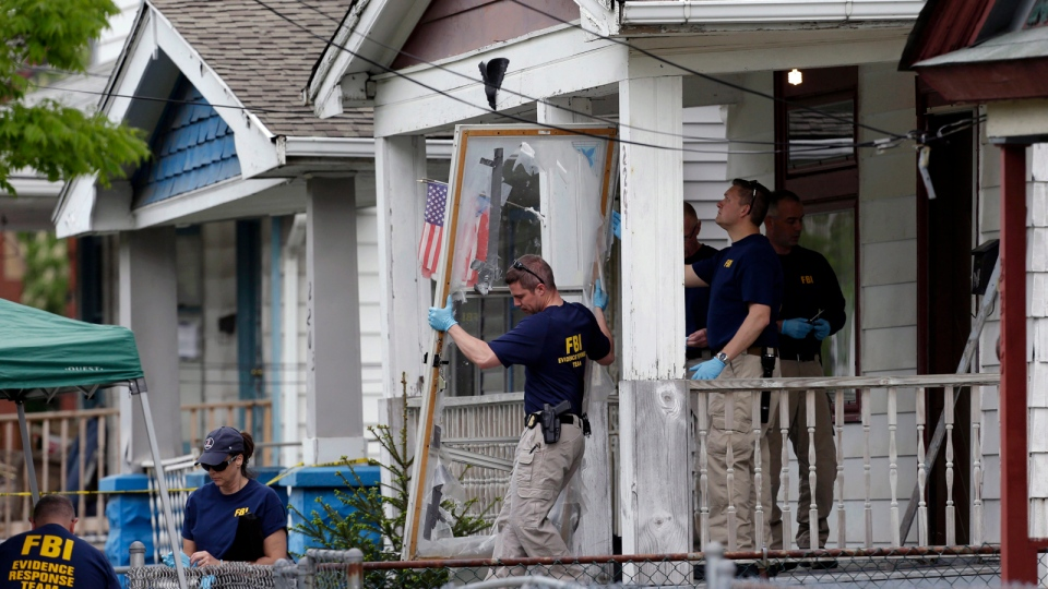 In this file photo, members of the FBI evidence response team carry out the front screen door from the Cleveland home of Ariel Castro, where three women escaped after 10 years of captivity, May 7, 2013. (AP / Tony Dejak, File)