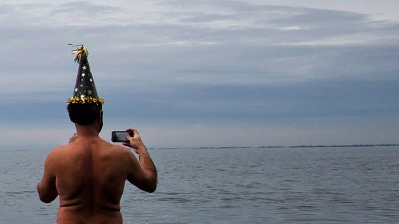 Don Pitcairn, president of the Surrey United Naturists, takes a photo of himself while standing in the waters of Boundary Bay in 2014. (Darryl Dyck/THE CANADIAN PRESS)