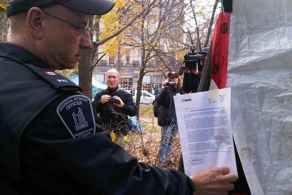 A Toronto bylaw officer places an eviction notice on the tent of an Occupy Toronto demonstrator at St. James Park, Tuesday, Nov. 15, 2011. (Jeff Wood / CTV News)