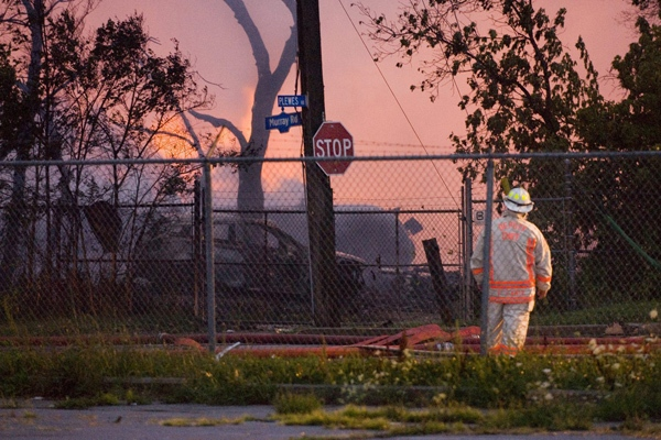 A firefighter surveys the scene of a propane explosion at Sunrise Propane in Toronto as dawn breaks on Sunday Aug. 10, 2008. (Angela Deluce / THE CANADIAN PRESS)