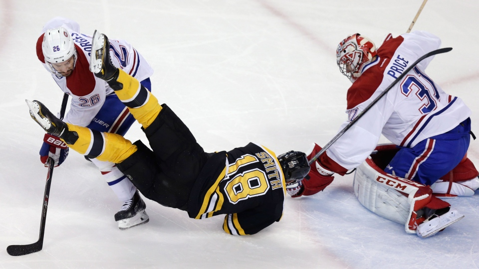Montreal Canadiens defenseman Josh Gorges (26) upends Boston Bruins right wing Reilly Smith (18) as goalie Carey Price makes a save during the first period in Game 7 of a second-round NHL hockey Stanley Cup playoff series in Boston, Wednesday, May 14, 2014. (AP)