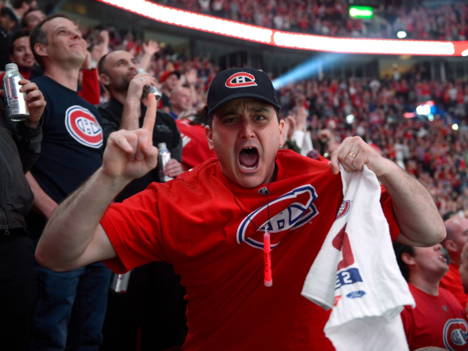 A Montreal Canadiens fan reacts to the NHL action against the Boston Bruins on a giant-screen in Montreal Wednesday May 14, 2014. Montreal's Bell Centre was a sea of red, white and blue on Wednesday night as Canadiens fans packed the arena to watch their beloved Habs play 500 kilometres away.THE CANADIAN PRESS/Ryan Remiorz