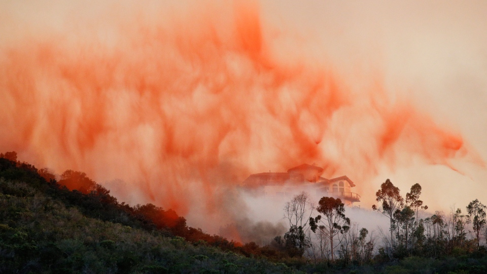 A plane drops fire retardant over a hot spot in San Marcos, Calif. on Wednesday, May 14, 2014. (AP)