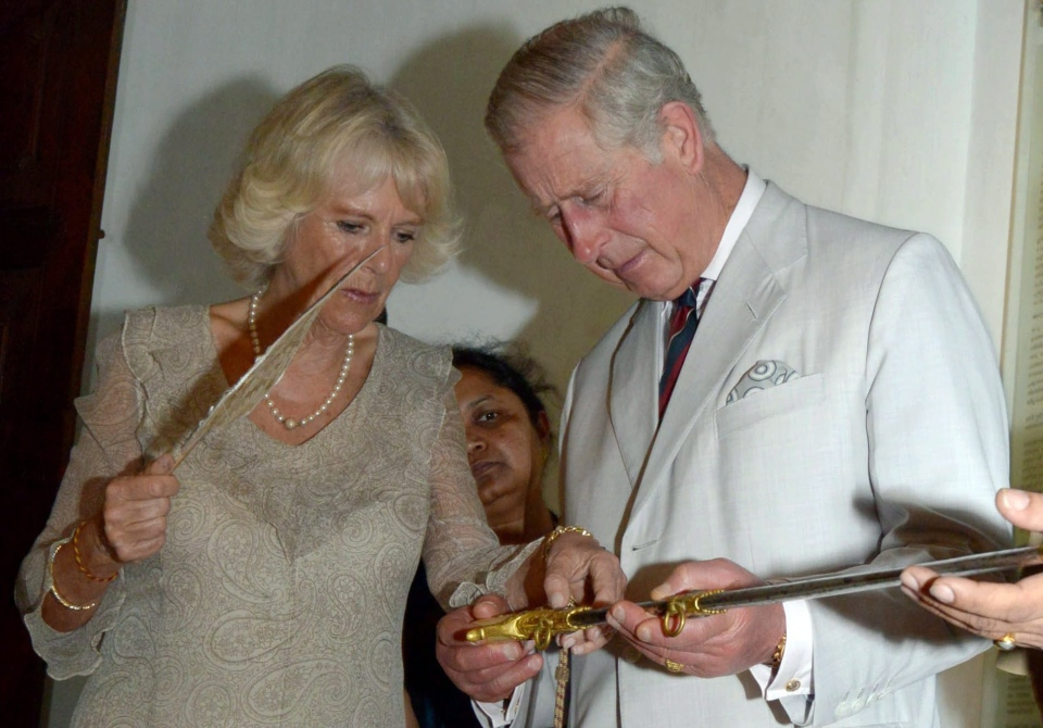 Prince Charles puts down a sword after examining it, as his wife Camilla, the Duchess of Cornwall, stands beside him, at the Mattancherry Palace, where historical artifacts are showcased, in Kochi, India, Thursday, Nov. 14, 2013. (Kerala Information and Public Relations Department)