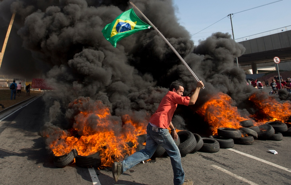 A member of the Homeless Workers Movement carries a Brazilian flag past burning tires during a protest against the money spent on the World Cup near Itaquerao stadium which will host the international soccer tournament's first match in Sao Paulo, Brazil, Thursday, May 15, 2014. (AP / Andre Penner)