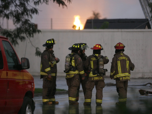 Firefighters gather several blocks from a five-alarm blaze at a propane refinery in northwest Toronto, Sunday, August 10, 2008. (J.P. Moczulski / THE CANADIAN PRESS)