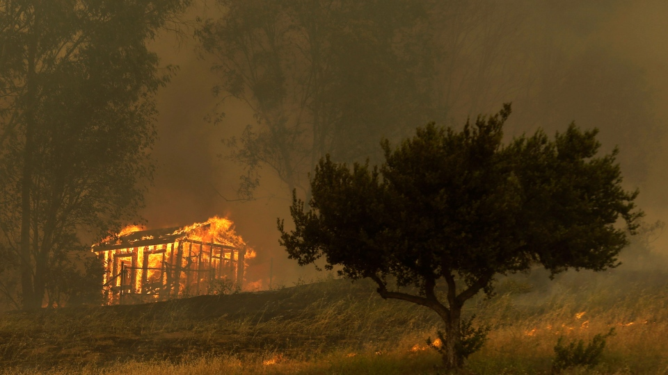 Fire engulfs a structure during a wildfire in Escondido, California on Thursday, May 15, 2014. (AP / Gregory Bull)