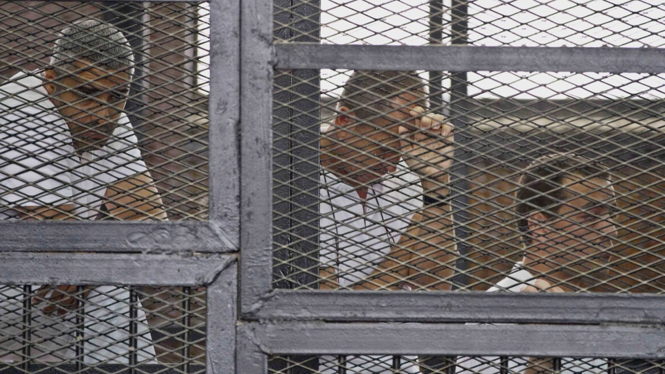 Mohammed Fahmy, Canadian-Egyptian acting bureau chief of Al-Jazeera, from left, Australian correspondent Peter Greste and Egyptian producer Baher Mohamed appear in a defendant's cage along with several other defendants during their trial on terror charges at a courtroom in Cairo, Egypt, Thursday, May 15, 2014. (AP / Hamada Elrasam)
