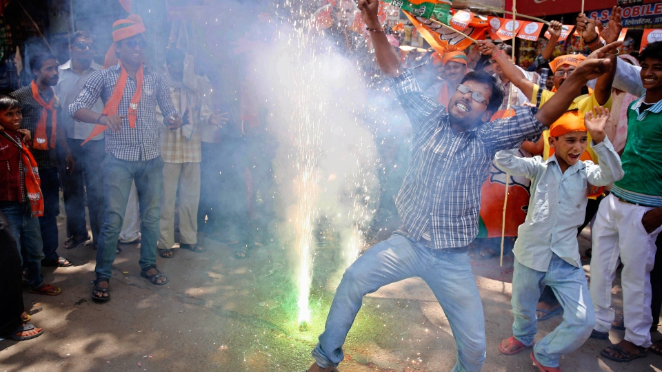 Bharatiya Janata Party (BJP) supporters dance and burst firecrackers to celebrate the news of early election result trends in Allahabad, in the northern Indian state of Uttar Pradesh, Friday, May 16, 2014. (AP / Rajesh Kumar Singh)