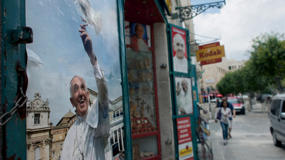 In this Monday, May 12, 2014 photo, a tourist couple walk past a gift shop decorated with pictures of late Pope John Paul II and Pope Francis near the Church of the Nativity, one of the stops of Pope Francis during his upcoming visit in the Holy Land at the end of this month, in the West Bank city of Bethlehem. (AP / Nasser Nasser)