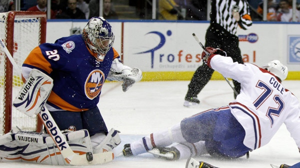 New York Islanders goalie Evgeni Nabokov (20) blocks a shot as Montreal Canadiens right wing Erik Cole (72) slides into the crease in the first period of their NHL hockey game at Nassau Coliseum in Uniondale, N.Y., Thursday, Nov. 17, 2011. (AP Photo/Kathy Willens)