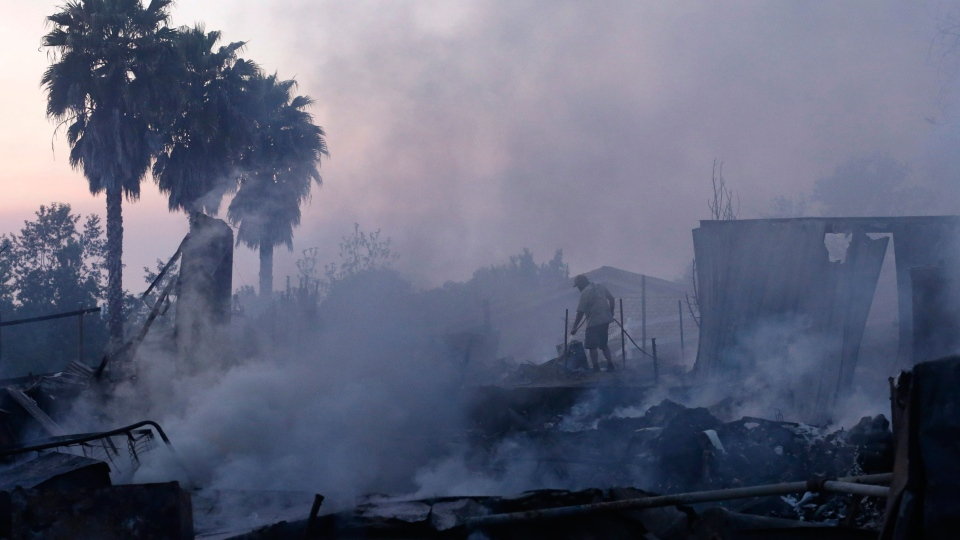 Jeff Buchanan waters the scorched earth around a neighbor's house that burned to the ground during a wildfire Thursday, May 15, 2014, in Escondido, Calif. (AP / Gregory Bull)