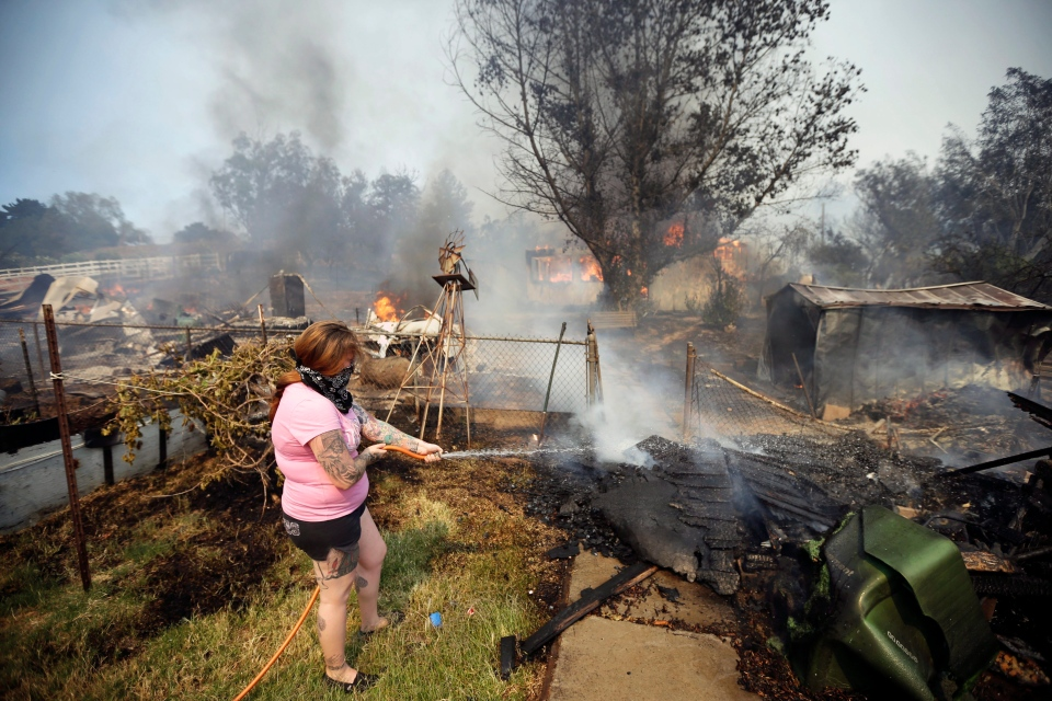 A woman douses water from a hose around her home as her neighbor's home burns during a wildfire Thursday, May 15, 2014, in Escondido, Calif. (AP / Gregory Bull)