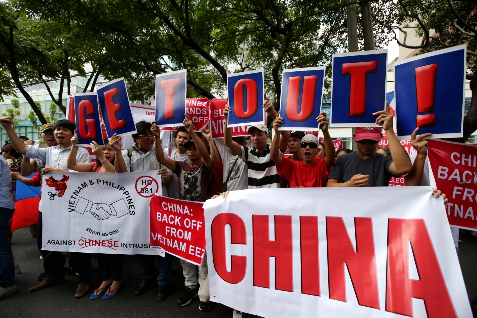 Vietnamese expatriates and Filipinos display placards as they join together in a rally in front of the Chinese Consulate at the financial district of Makati city to protest the recent moves by China to construct an oil rig near the Vietnamese-claimed Paracels off the contested Spratlys group of islands and shoals in the South China Sea on Friday, May 16, 2014. (AP / Bullit Marquez)