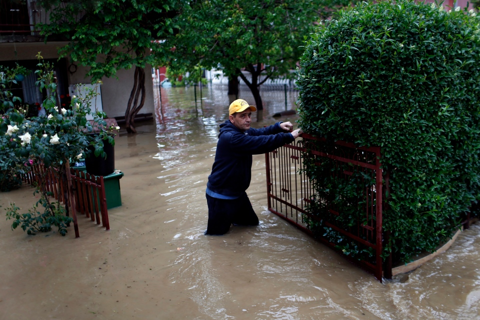 A man stands in front of his house hit by severe floods in Serbia on Friday, May 16, 2014. Rain-swollen rivers across the Balkans have flooded roads, cut off power and caused more than 200 landslides. (AP / Marko Drobnjakovic)
