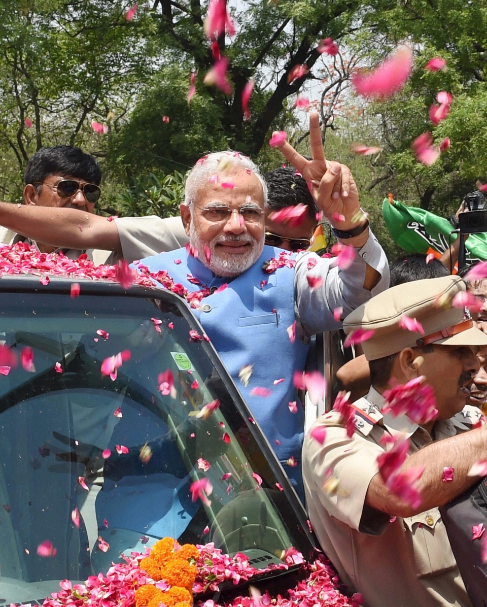 Supporters shower flower petals on India's next prime minister, Narendra Modi, as he arrives at the party headquarters in New Delhi, India on Saturday, May 17, 2014. (AP Photo)