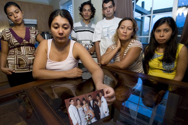 Patricia Villanueva holds a photo of her brother Freddy Villanueva, (left in picture) on Sunday Aug. 10, 2008, as her family gathers around her. (Peter McCabe / THE CANADIAN PRESS)