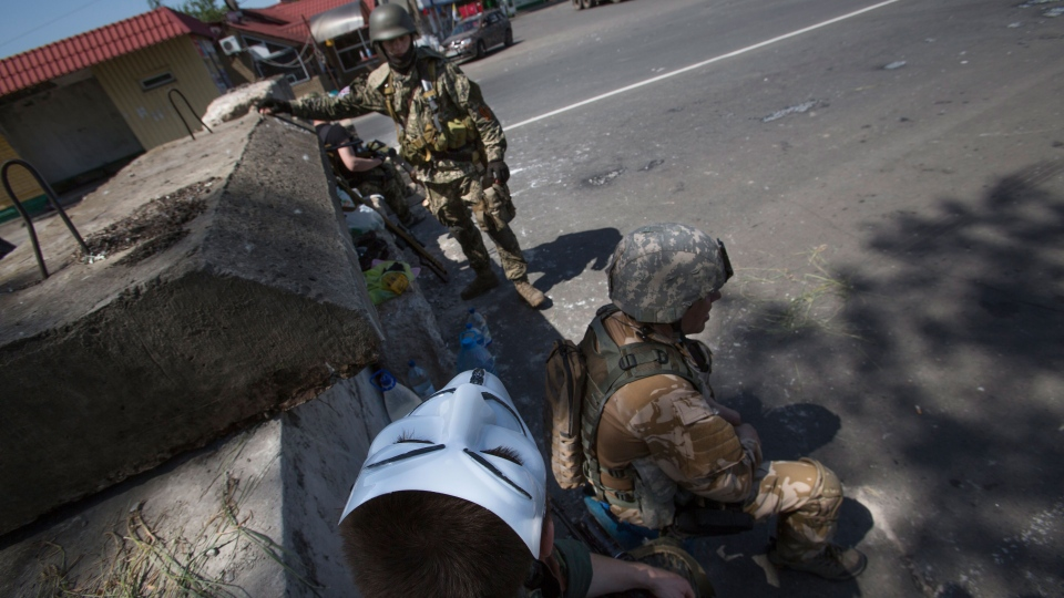 Pro-Russian militants rest behind the barricades as they guard a checkpoint blocking the major highway which links Kharkiv, outside Slovyansk, eastern Ukraine on Saturday, May 17, 2014 (AP / Alexander Zemlianichenko)