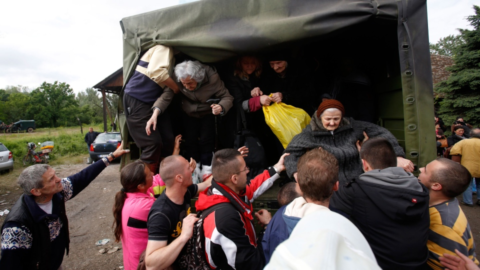 People help old women out of a military truck during evacuation from Obrenovac, some 30 kilometers (18 miles) southwest of Belgrade Serbia on Saturday, May 17, 2014. (AP / Darko Vojinovic)