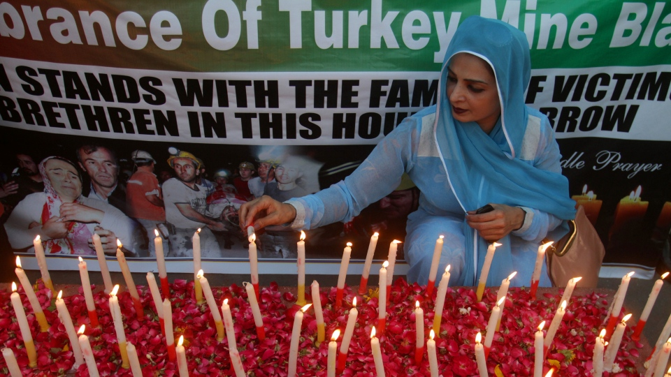 A member of the Lawyer Strategic Council of Pakistan lights a candle at a vigil to commemorate the Soma, Turkey mine accident victims, in Lahore, Pakistan on Saturday, May 17, 2014. (AP / K.M. Chaudary)