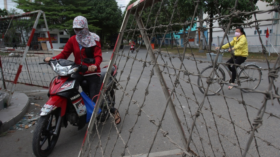 People drive past barbed-wire barricades at entrance of an industrial park in Binh Duong province, Vietnam Saturday, May 17, 2014, after mobs attacked foreign owned factories following anti-China protests. (AP / Hau Dinh)