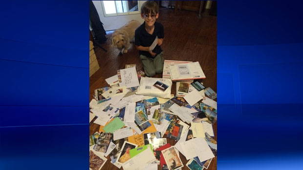 Ben Pierce, 9, is pictured with dozens of postcards and photos he's received from around the world. (Ben's Wish List / Facebook)