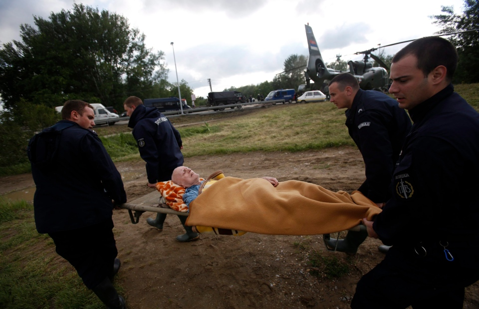 Serbian police officers carry a man from a military helicopter during flood evacuation from Obrenovac, some 30 kilometers southwest of Belgrade Serbia on Saturday, May 17, 2014. (AP / Darko Vojinovic)