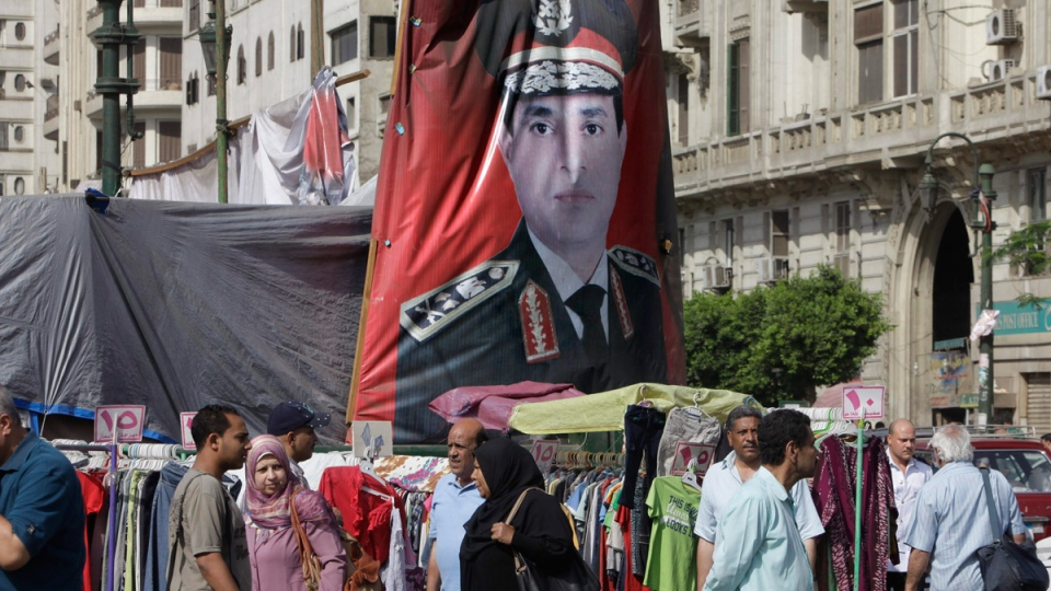 Egyptians walk past a banner with a portrait of Egyptian Presidential hopeful Abdel-Fattah el-Sissi at a market in Cairo, Egypt, Saturday, May 17, 2014. (AP Photo/Amr Nabil)
