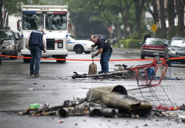 Montreal police officers search for evidence and clean up after weekend rioting in the city's north end, Monday, Aug. 11, 2008. (Peter McCabe / THE CANADIAN PRESS)