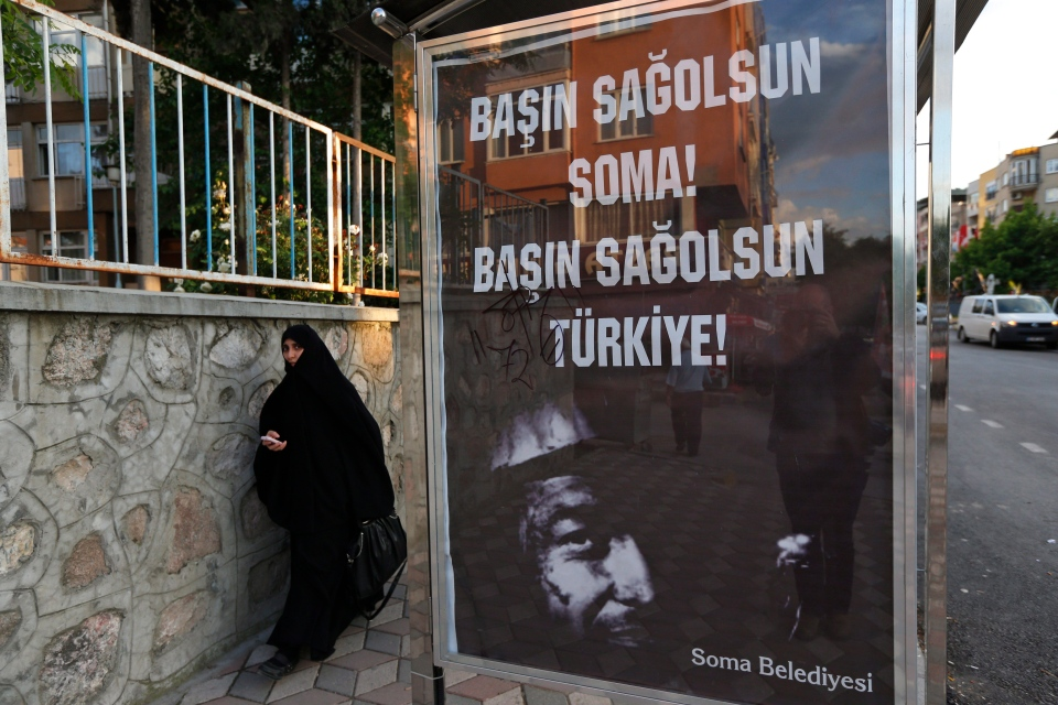 A woman walks past a bus stop with a poster offering condolences over the Turkish mining disaster on Saturday, May 17, 2014. (AP / Lefteris Pitarakis)