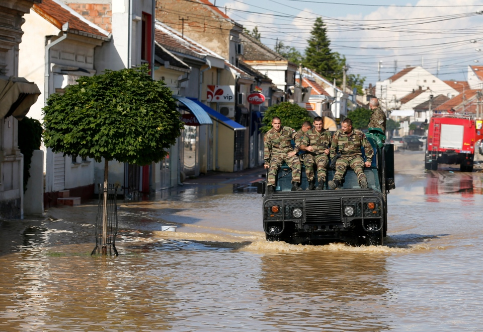 A police vehicle drives through a flooded street in Obrenovac, some 30 kilometers southwest of Belgrade, Serbia, Sunday, May 18, 2014. In Serbia, more than 20,000 people have been forced from their homes. (AP Photo/Darko Vojinovic)